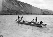 A group of people in a scow on the Pelly River near Ross River, trying out the engine.